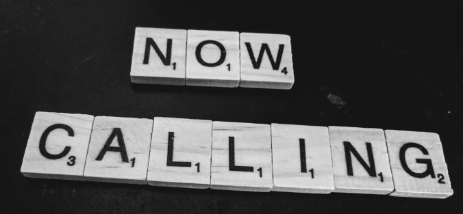 "Scrabble tiles on a black background, spelling out ""Now Calling"""