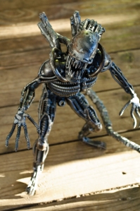 A toy xenomorph from the film Alien standing on wood.