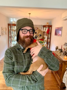 A photo of Matthew T. Jones with his small brown dog.