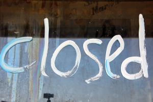 "the word ""closed"" painted in white on glass"
