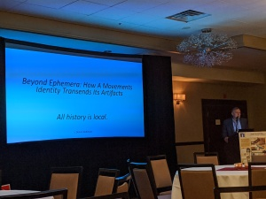 "A picture of Tom Kaufhold standing at a podium with a screen next to him with his presentation title: ""Beyond Ephemera: How a Movement's Identity Transcends Its Artifacts"""