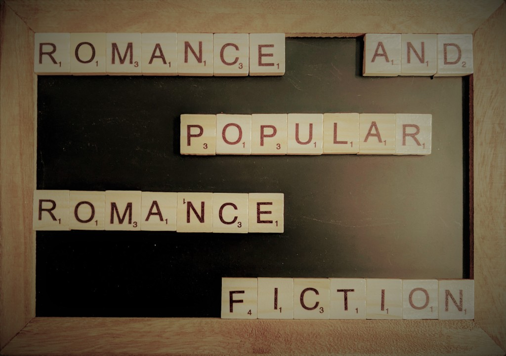 """A chalk board with scrabble tiles that spell out """"Romance and Popular Romance Fiction""""."""